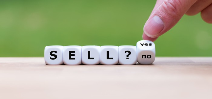 "Die spelling ""Sell?"" with a person's fingers holding another dice at an angle to display ""yes' on one side and ""no"" on another side"