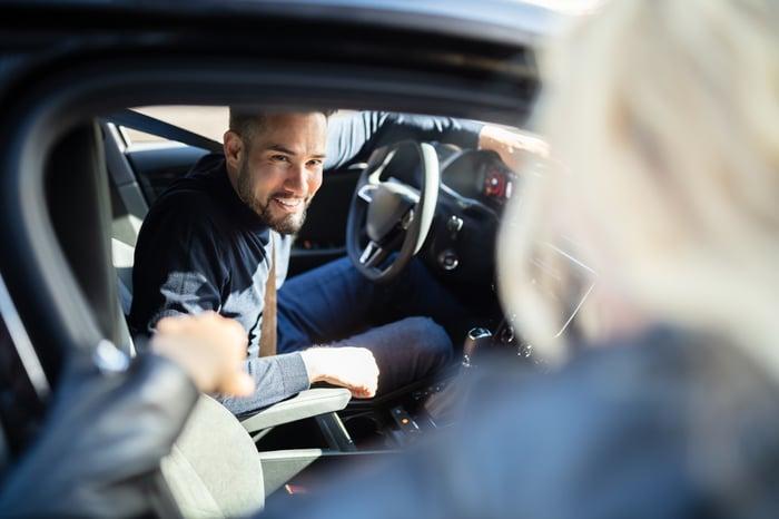Smiling man in car speaking to woman