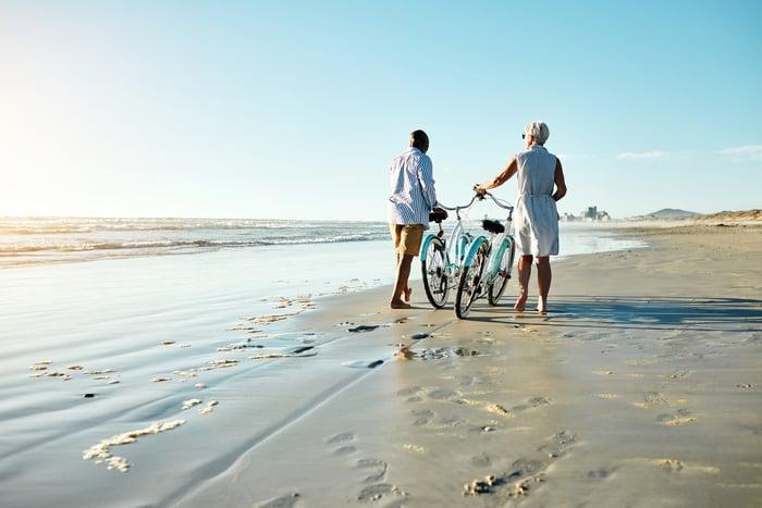 An older couple walking their bikes on the beach