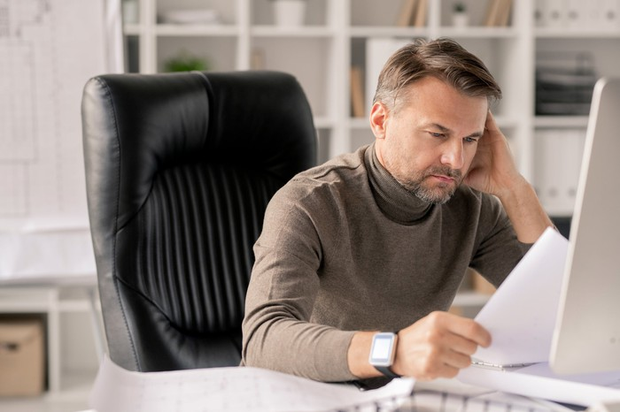 Man with serious expression sitting at a desk in front of a computer and holding papers.