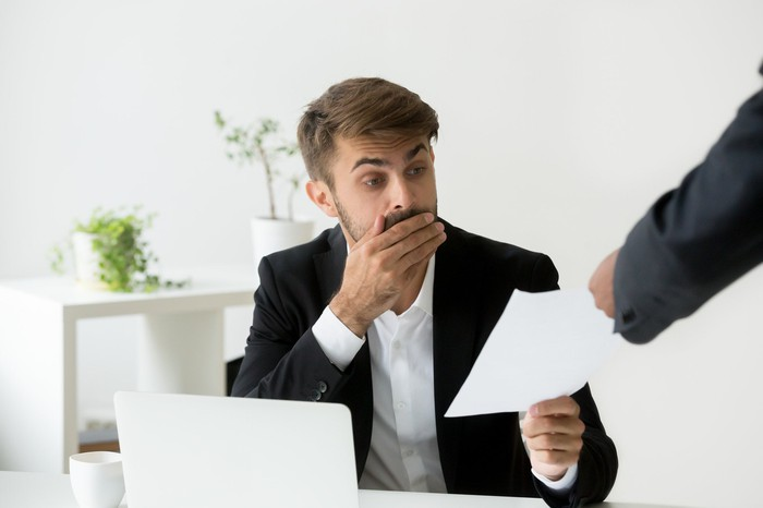 Man in suit covers his mouth in shock as he reviews document someone is handing him.