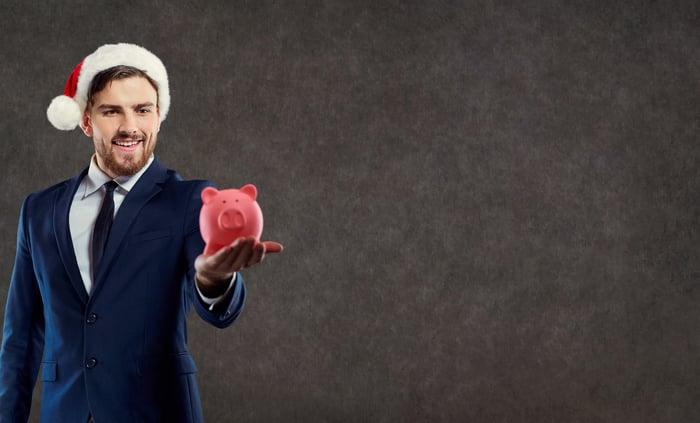 A businessman in a Santa hat holds a piggybank.