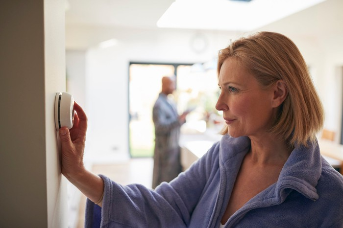 A woman adjusting a thermostat.