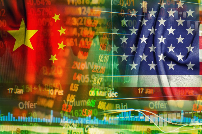 Representations of flags from US and China overlaid with stock market ticker symbols.