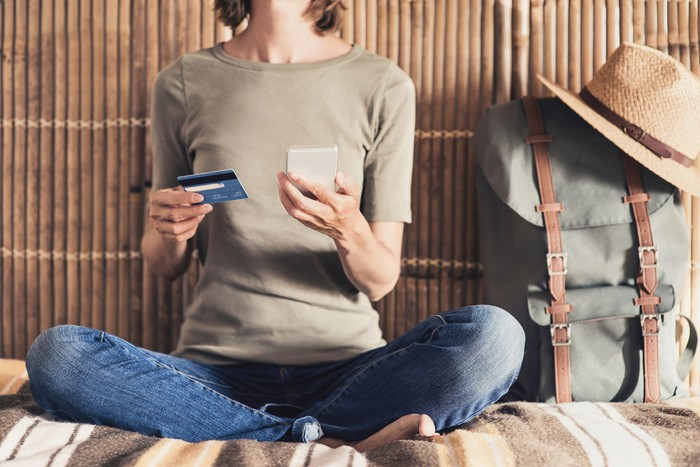 A woman sitting on a bed next to a backpack holds a credit card in one hand and a phone in the other.