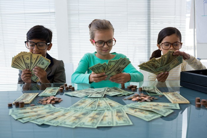 Three young children wearing glasses and playing with piles of money.