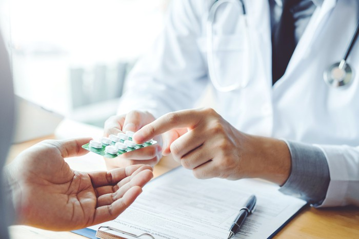 Physician pointing at some pills.