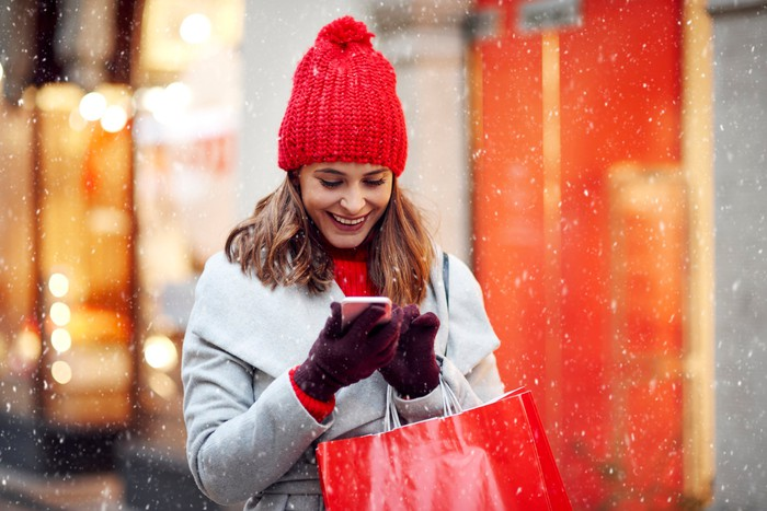 Smiling woman with shopping bags looking at phone in snow
