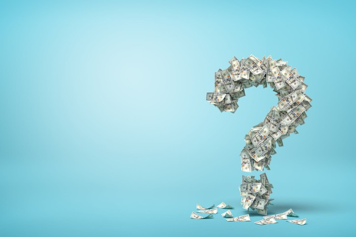 Question mark made of cash with a light blue background