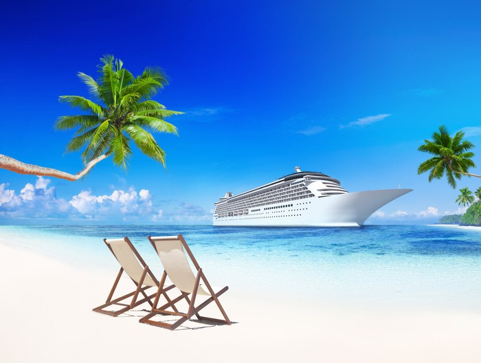 A cruise ship on a tropical bay with  two beach chairs in the sand in the foreground.