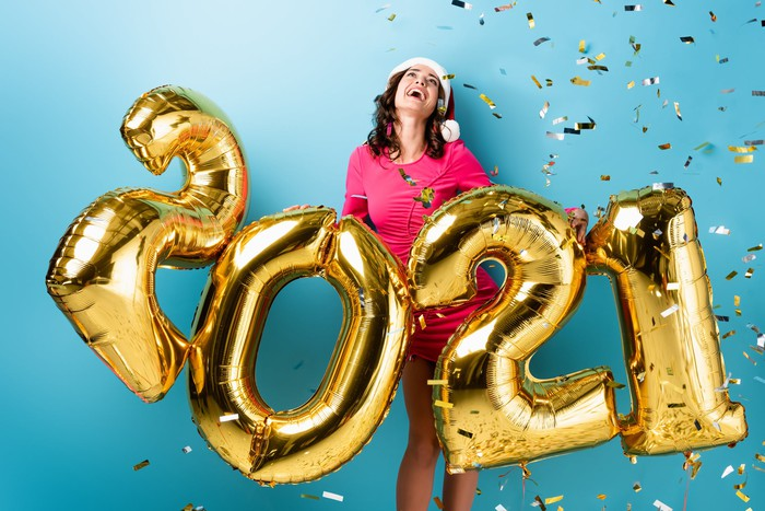 A woman celebrating the new year with 2021 balloons and confetti in the air.