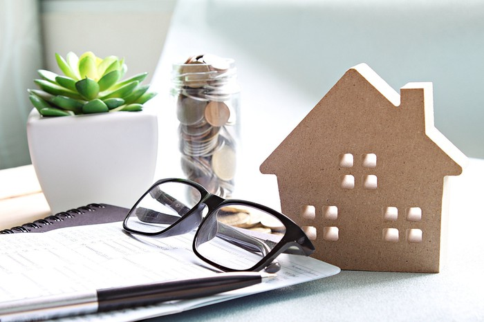 A pair of glasses, jar of coins, and miniature model home situated together on a table top.