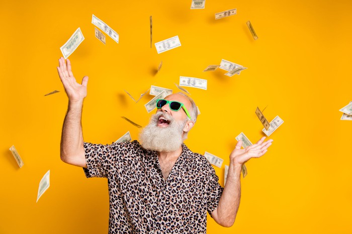 A man with a white beard smiles as money rains down on him.