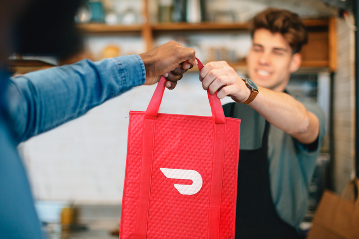 Man wearing apron handing red bag with DoorDash logo on it to a person