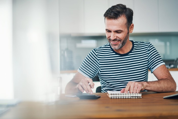 Smiling man resting hand on notebook while typing on calculator