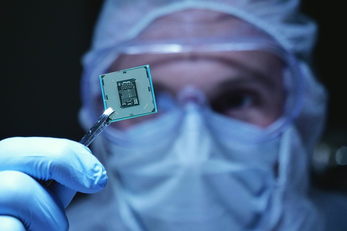 A fab worker holds up a small processor with tweezers in front of her eyes.