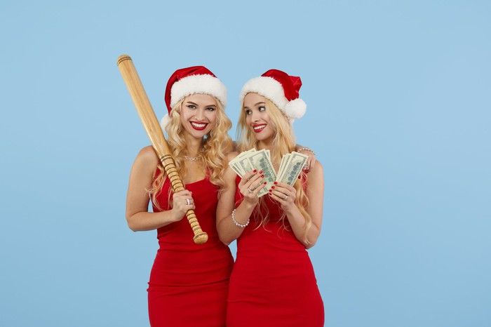 Two women wearing Santa caps. One is holding a baseball bat. The other is holding money.