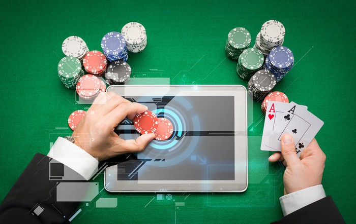 Online casino concept showing a man's hands placing poker chips on a tablet screen, while holding a pair of aces.
