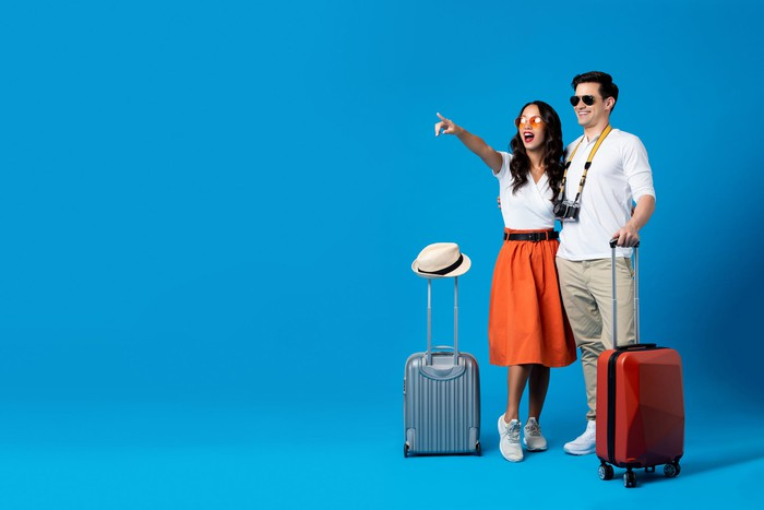 A young couple with suitcases against a blue background. The woman points to something in the distance.