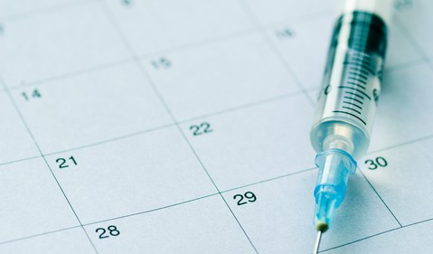 Syringe and needle on top of calendar