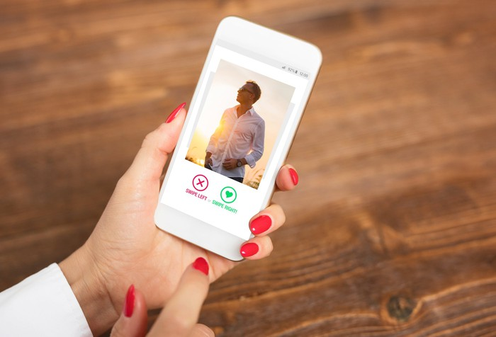 Lady holding a mobile in left hand while looking at a potential online date.