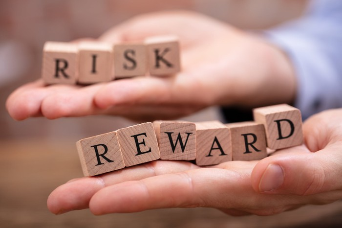 """One hand holding wood blocks spelling """"risk"""" and another hand holding wood blocks spelling """"reward"""""""