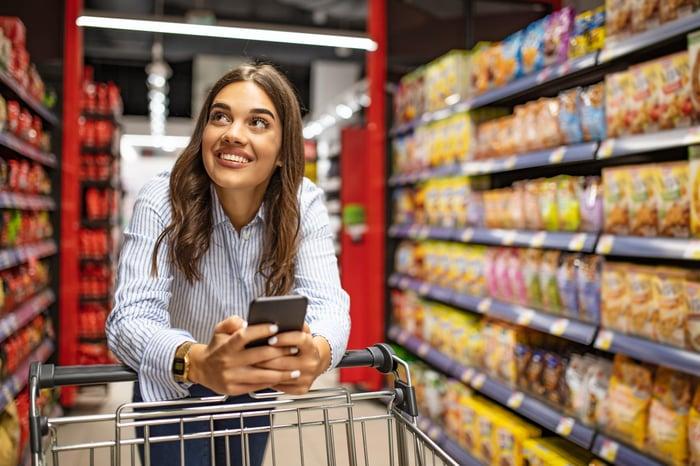A woman checks her phone as she pushes a shopping cart through a supermarket aisle.