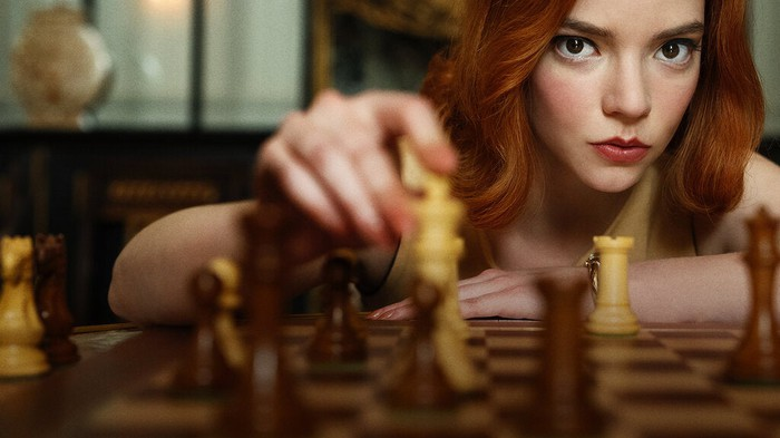 The Queen's Gambit star Anya Taylor-Joy holds a chess piece on the chess board.