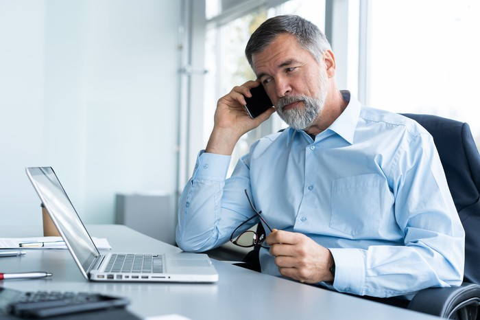 Older man at laptop on a cell phone
