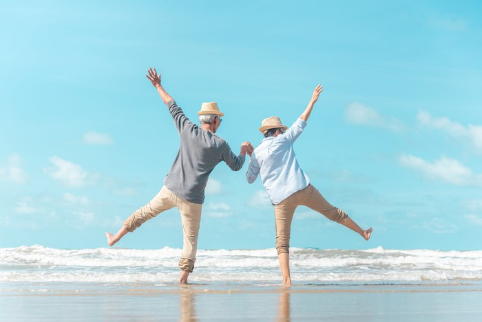 Older couple holding hands and dancing on the beach