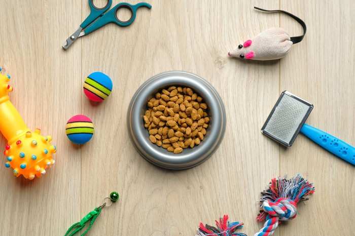 Assortment of various pet products, including toys, a food bowl, and a brush