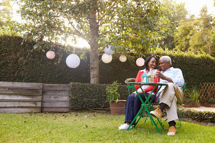 A couple sitting in chairs in a yard drinking wine.