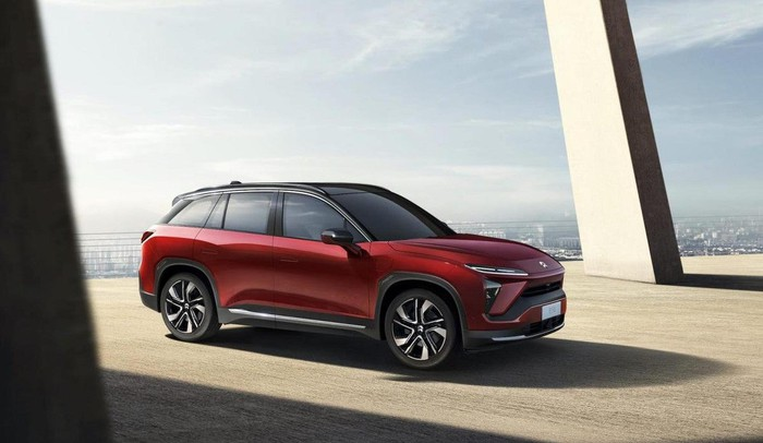 Red NIO electric SUV on a concrete platform, overlooking a city.
