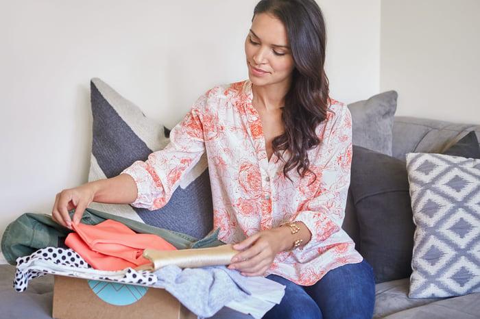 A woman opens her Stitch Fix box.
