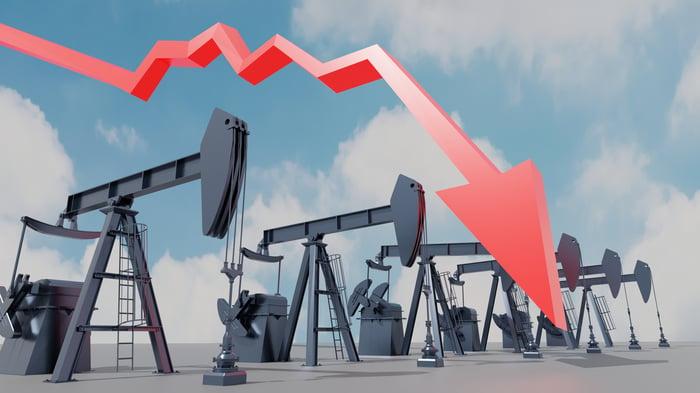 Downward arrow superimposed over oil pumpjacks