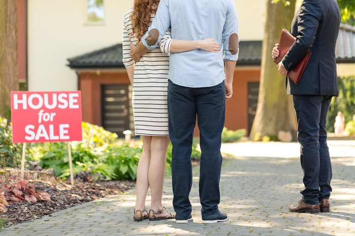 A couple standing by a home for sale with a real estate agent.