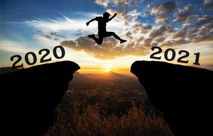 A person jumping from the 2020 cliff to the 2021 cliff with the sun setting in the background.