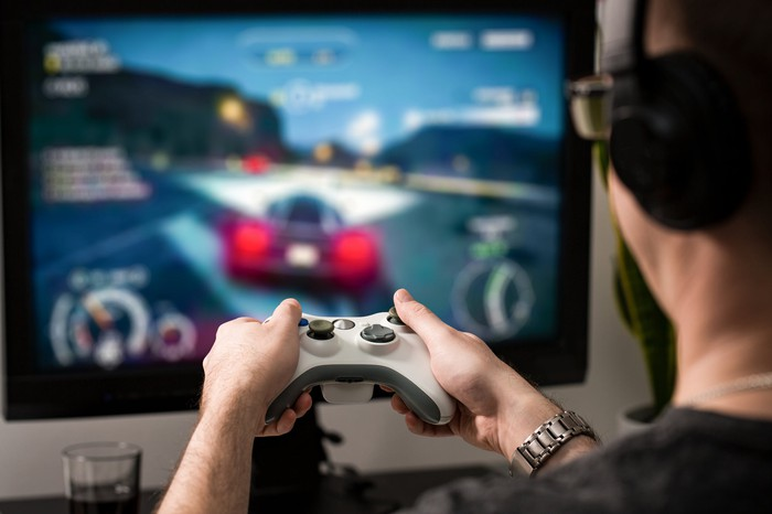 Photo of a bespectacled gamer holding a console controller in front of a large screen.
