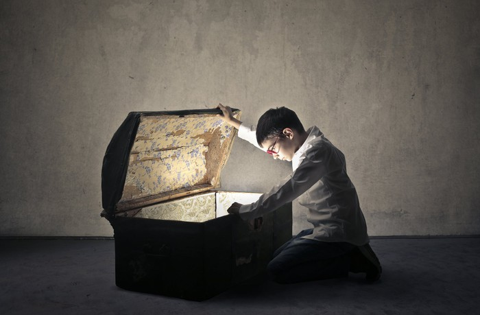 A young child looks down in an open treasure chest.
