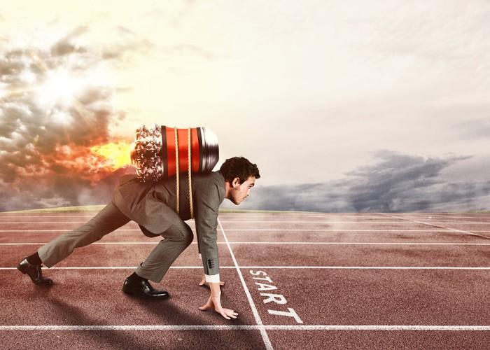 A businessman crouches at the starting line like a sprinter, wearing a fired-up jetpack on his back.