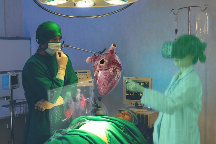 Two doctors in the operating room with a virtual heart hovering above the patient on the table.
