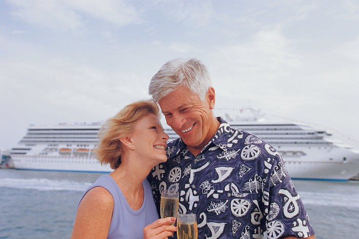 Couple drinking champagne and standing in front of a cruise ship.