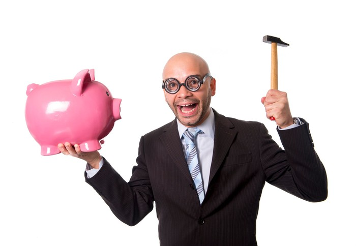 A man in a suit holding a hammer as if he is going to break a piggy bank.