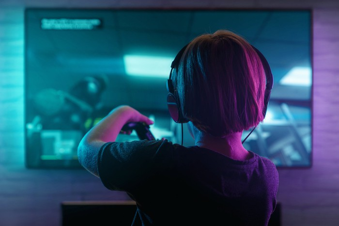 A child with headphones on playing a video game.