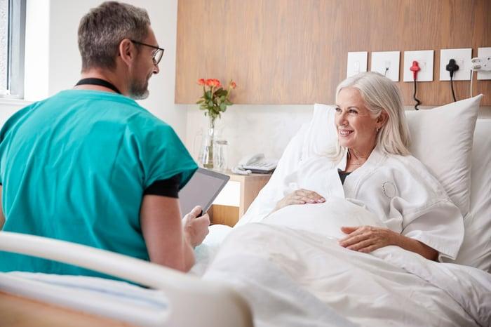Man in scrubs talking to older woman lying in bed