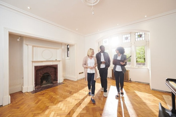 A couple speaking with their realtor while looking around the empty living room of a home.