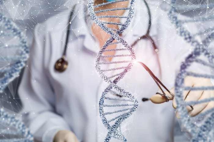 A doctor using small scissors to cut out a portion of the double helix DNA strand.