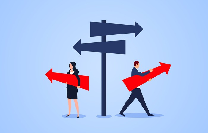 Man and woman holding arrows pointing in opposite directions near signpost