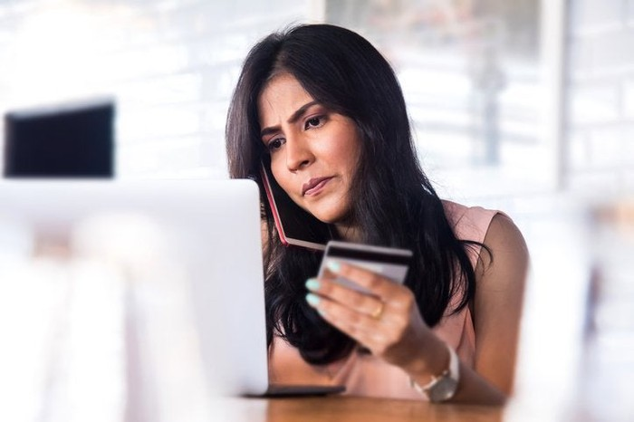Woman with cell phone to her ear and credit card in hand with look of concern on her face.