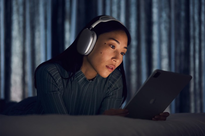 A woman wearing Apple's new AirPods Max headphones while using an iPad.